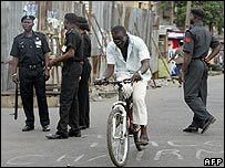 Man on bicycle cycles past police on patrol in Lagos
