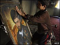 Iraqi child cleans portrait of Moqtada Sadr after US military raid