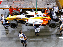 Heikki Kovalainen's Renault is lifted on to a crane after a mechanical failure