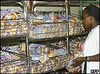 Woman shopping for bread in a shop in Harare