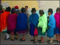 Indigenous Ecuadorians queue at a polling station for the referendum