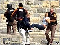 Полицейские выносят раненую девушку
