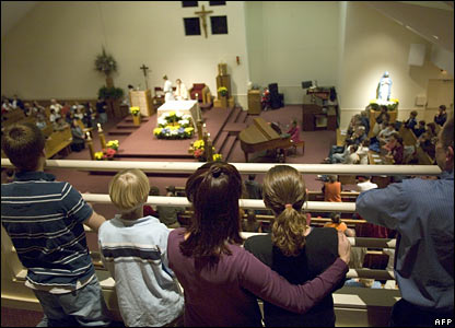 A family prays during a mass at St Mary's Church in Blacksburg, Virginia