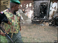Nigerian policeman looks at police station attacked during elections