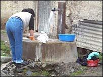 Mujer recolectando agua en Perú