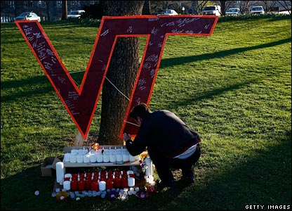 Student lighting candle underneath VT sign
