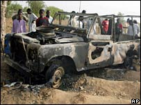 People looked at a vehicle destroyed by militants in Kano, northern Nigeria