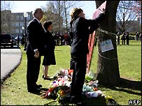 George Bush watches Laura Bush sign a memorial