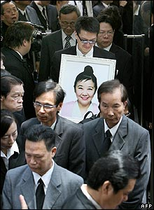 Wang's godson Anthony Cheung carries her portrait from the crematorium - 18/04/07