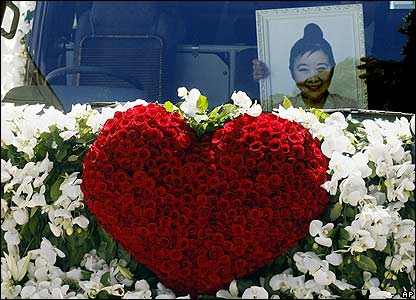 Picture of Wang at the front of the flower-covered hearse - 18/04/07