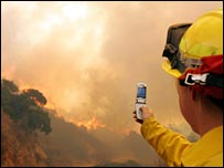 Man taking picture of a fire using mobile phone