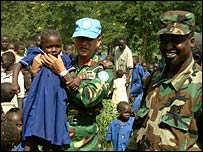 Gen Fazle Elahi Akbar (first from left) lifts a little girl on a visit to a school in Sudan (image by permission of Gen Akbar)