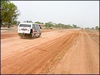 Minibus driving along bad road