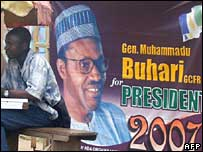 A man sit next to a poster for Muhammadu Buhari