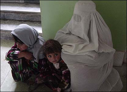 A woman holding a baby underneath her burkha waiting to be seen by a doctor