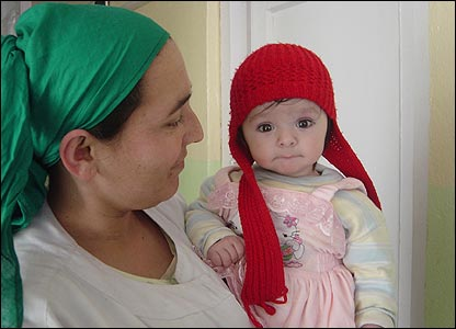 Female hospital worker holding a little girl