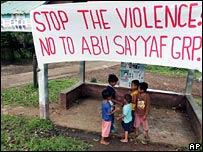 Children stand under a sign denouncing Abu Sayyaf in Jolo on 16 April 2007