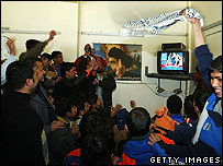Iraqi Shia Muslims celebrate as they watch footage of Saddam execution