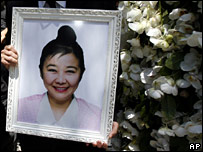 A mourner holds a picture of the late Nina Wang at her funeral on 18 April 2007