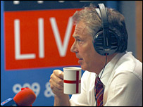 Tony Blair drinks from a St George's cross cup in a BBC radio studio