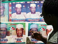 Mans looks at posters of presidential candidates