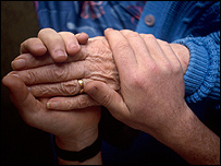 A carer holds the hand of an elderly person