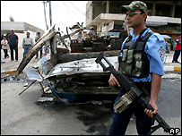 Iraqi policeman next to car bomb wreckage - file photo