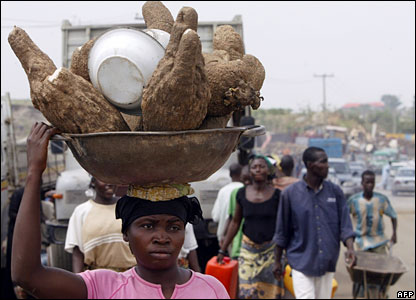 A woman carrying a pot of yams on her head