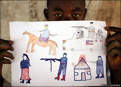 A boy in Chad hold up a picture of fighting he has witnessed