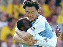 Darius Vassell celebrates with Sun Jihai after putting Man City ahead