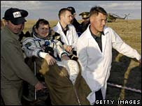 Space tourist Charles Simonyi is carried in his chair to a medical tent after landing, 21 April 2007