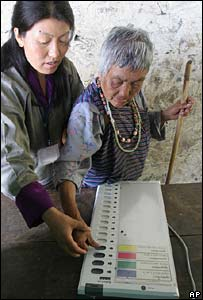 A polling official helps an elderly woman cast her vote during a mock poll at a polling station in Bangtsho, Bhutan, 21 April 2007