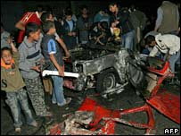 Palestinians gather round a car destroyed in the Israeli missile strike