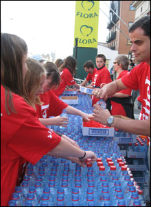 Kids help out at a water station in the London marathon