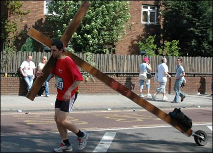 Runner dragging a wooden cross in the London Marathon