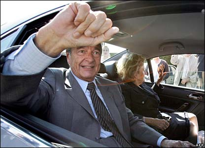 President Jacques Chirac waives from a car after voting in Sarran, central France