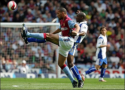Aston Villa's John Carew and Portsmouth's Sol Campbell battle for the ball