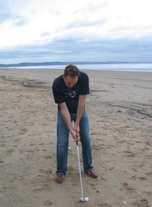 John Cropley playing golf on the beach