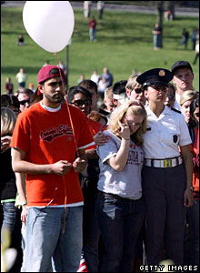 A man holds a white balloon, one of 32 released, one for each of the 32 victims