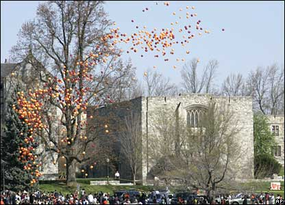 Orange and maroon balloons float over Norris Hall