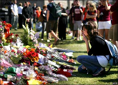 A girl kneels beside flowers left for the victims at Virginia Tech
