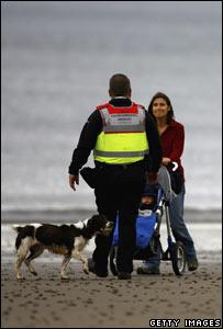Warden approaching woman on beach