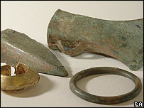 A gold lock ring, a spearhead blade, a socketed axe head and a bracelet found by John Minns