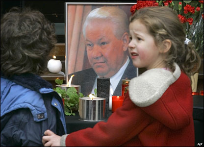 Woman and child in front of portrait of Boris Yeltsin