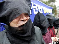 North Korean defectors, wearing hoods to conceal their identities, hold a rally for the three teenagers in front of the Laos embassy in Seoul - 13/04/07