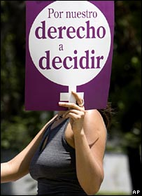 A Mexican woman holds a banner which reads: For our right to decide