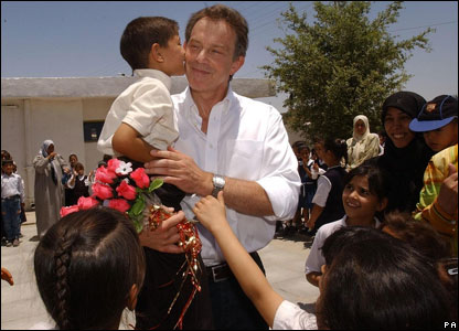 Abbas Adnan, plants a kiss on The British Prime Minister, Tony Blair's cheek, as he is greeted by school children in Basra, 2003