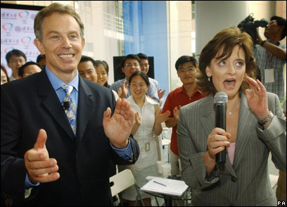 "British Prime Minister Tony Blair reacts as his wife, Cherie, sings 'When I""m 64"" by The Beatles to students at Tsinghua University in Beijing, 2003"