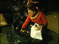 Joven recoge alimentos de la basura