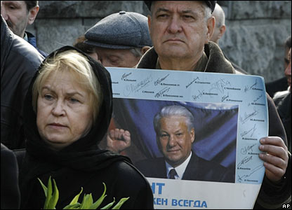 A man holding a picture of Mr Yeltsin waits in line to pay his respects